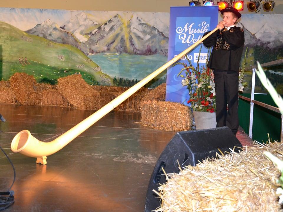 Pascal Barmettler mit Alphorn und vor der Kulisse des Bühnenbilds am Nationalen Final des Wettbewerbs «Folklorenachwuchs 2013».