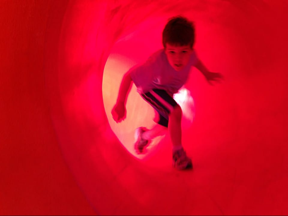 Junge in rotem Tunnel.
