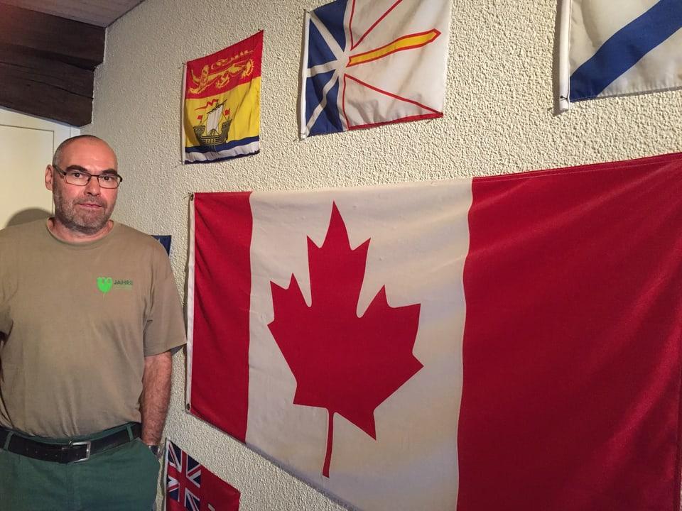 Thomas Steinemann vor seiner Flaggenwand mit Erinnerungsstücken an zahlreiche Reisen.