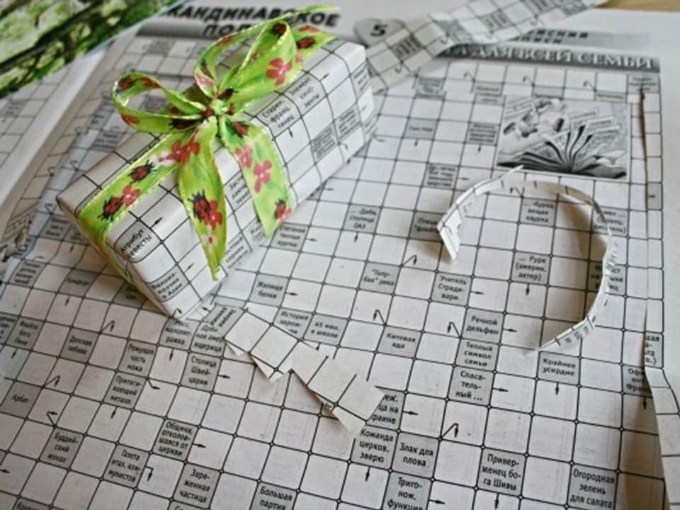 Päckli in ein Kreuzworträtsel gewickelt mit grüner Schlaufe.