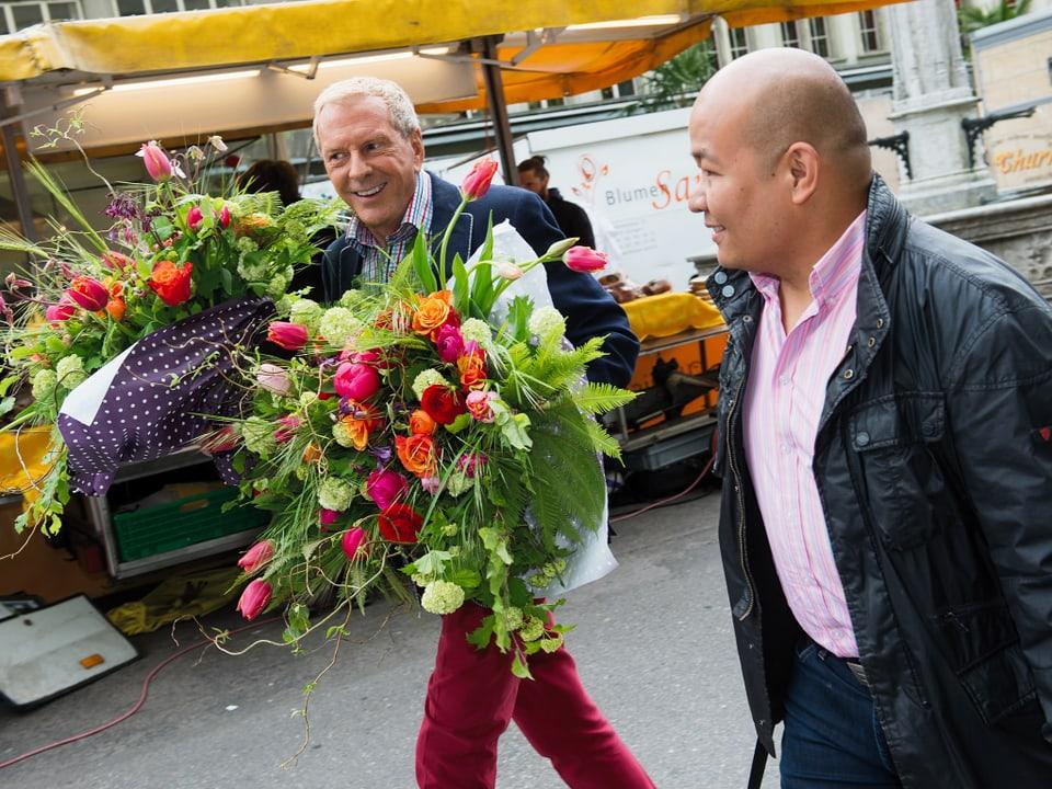 Kurt Aeschbacher, schwer beladen mit je einem Strauss Blumen in den Händen. Die Sträusse sind in rot gehalten, unter anderem Rosen und Tulpen, eingewickelt in weiss getupftes, blaues Papier. Domingo Domingo geht nebenher.