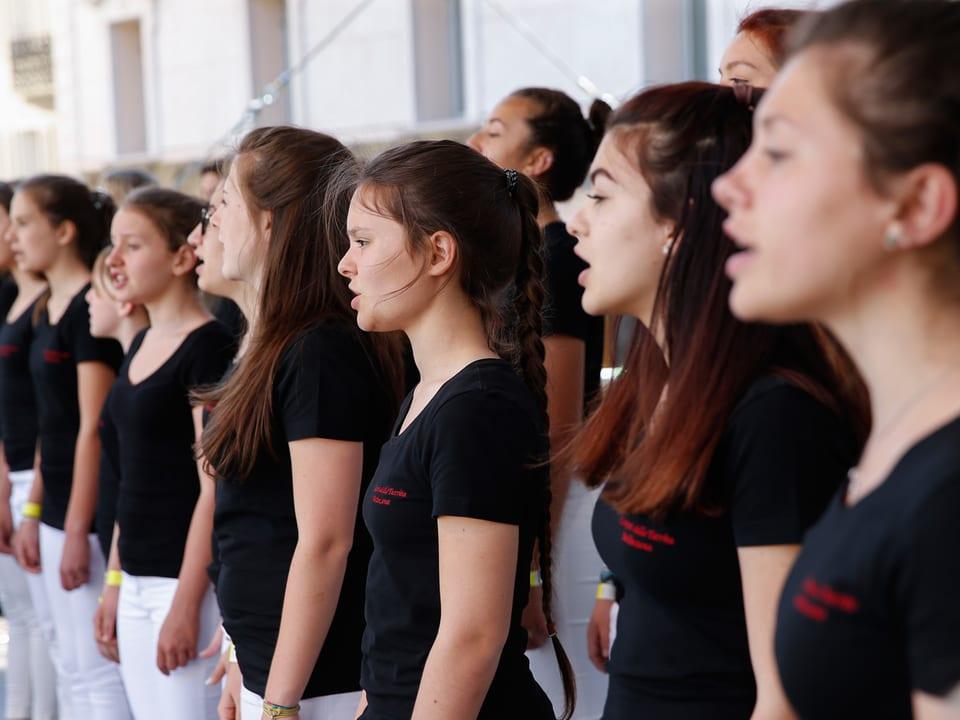 Junge Sängerinnen in schwarzen T-Shirts und weissen Hosen.