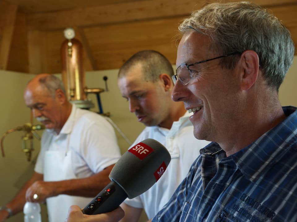 Im Hintergrund füllen zwei Männer Flaschen ab, während Robert Manser im Vordergrund ein Interview gibt.
