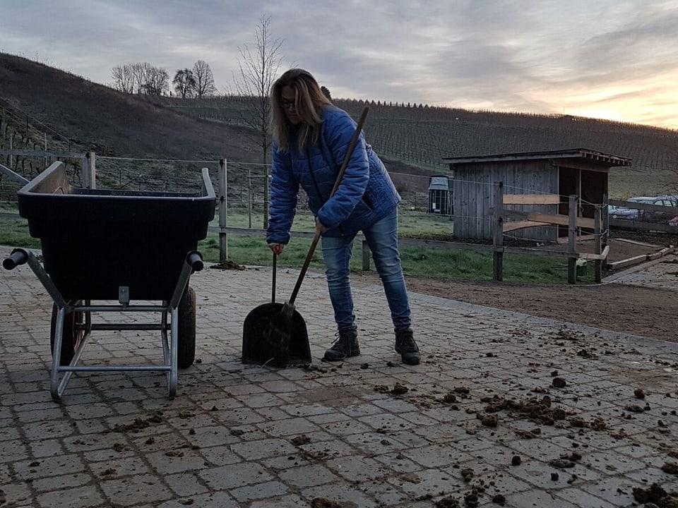 Frau wischt Pferdemist zusammen.