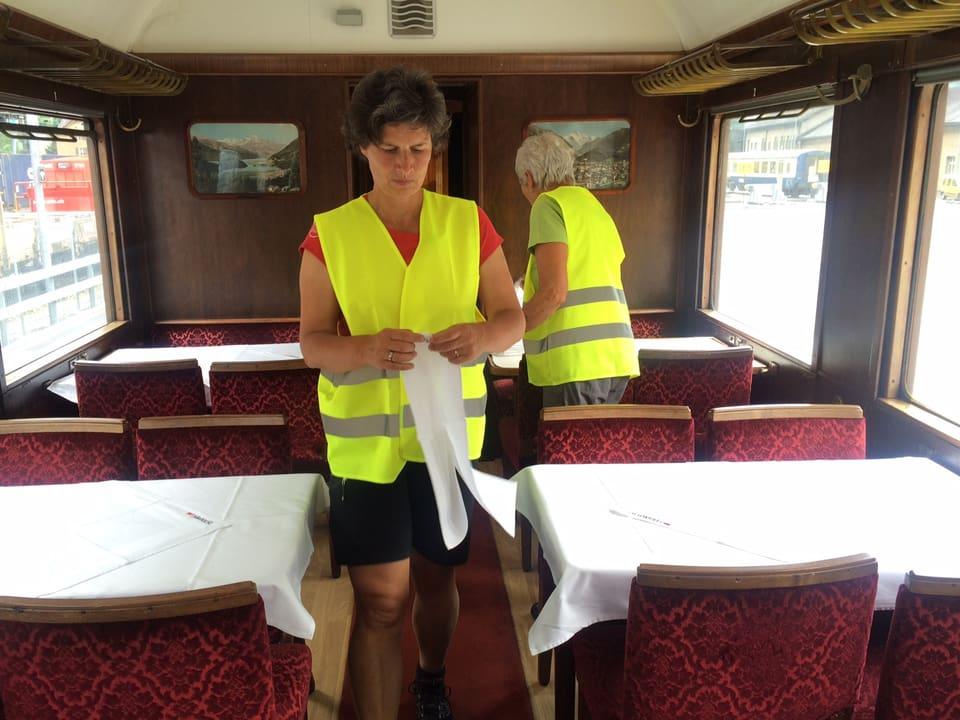 Frauen decken Tische in einem Zug mit weissen Tischtüchern