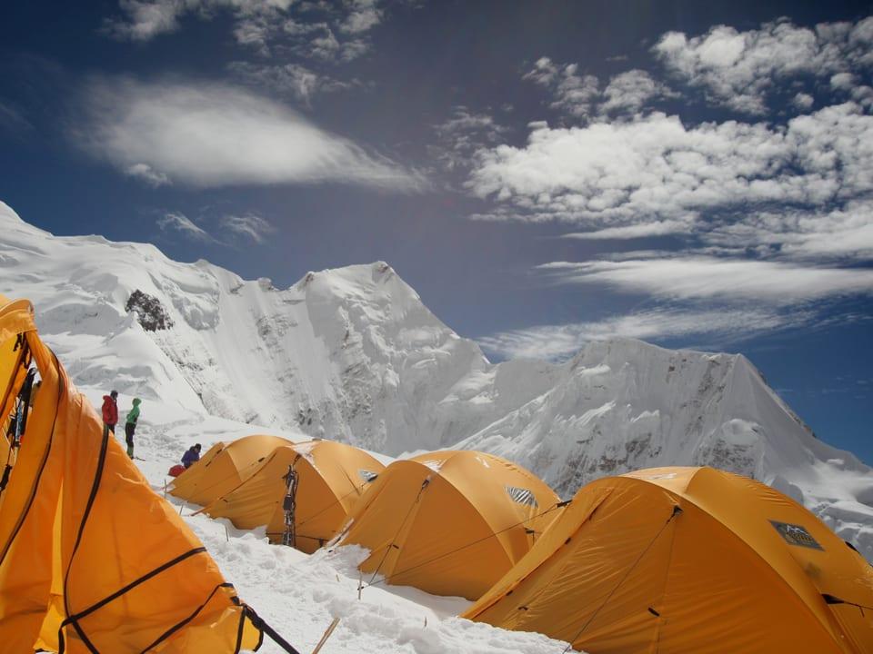 Gelbe Zelte im Hintergrund das Bergmassiv im Himalaya.