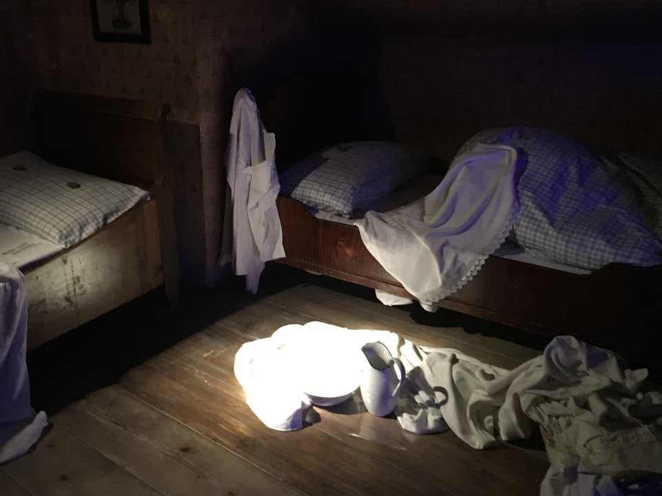 Das Dienstmädchenzimmer mit Bett und Wasserbecken am Boden. Es ist beinahe dunkel hier drin.