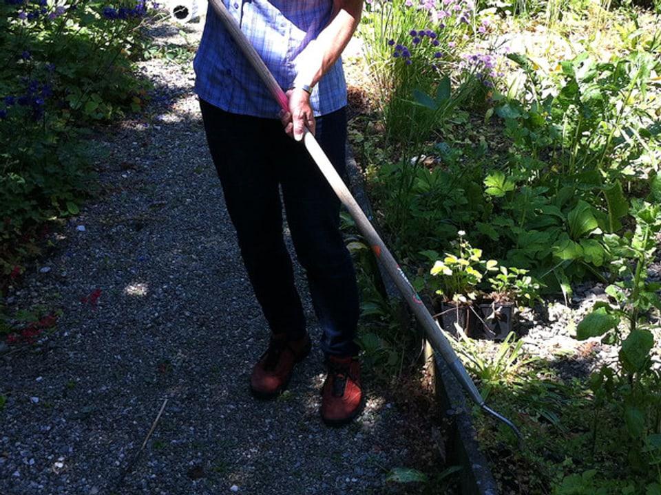 Gartenhacker mit langem Stiel im Einsatz.