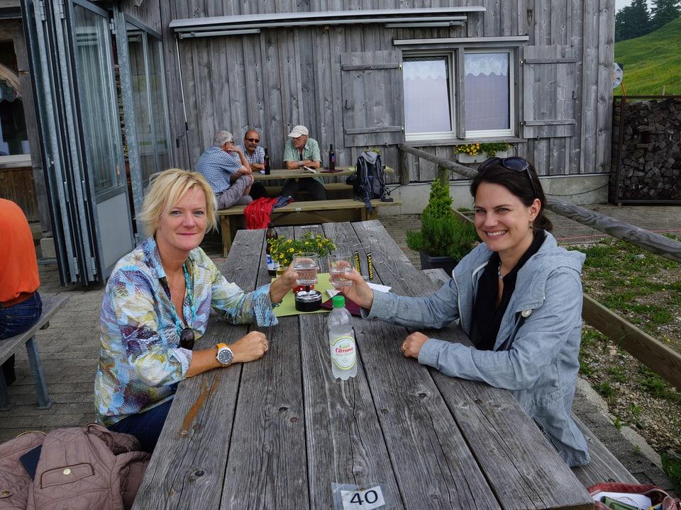 Die beiden Frauen sitzen an einem Holztisch in der Gartenwirtschaft und prosten sich mit einem Glas zu.