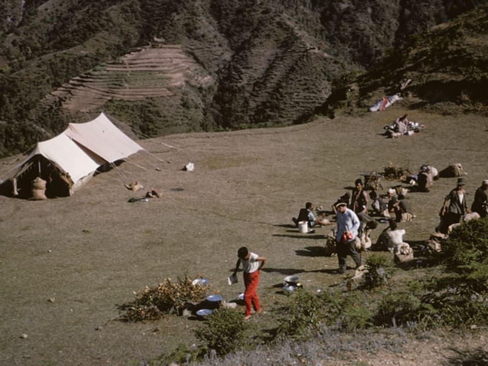Zelt in einer Ebene, daneben einige Menschen.