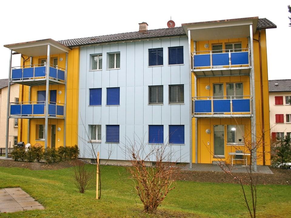 Wohnblock in den Farben gelb und hellblau mit blauen Storen.