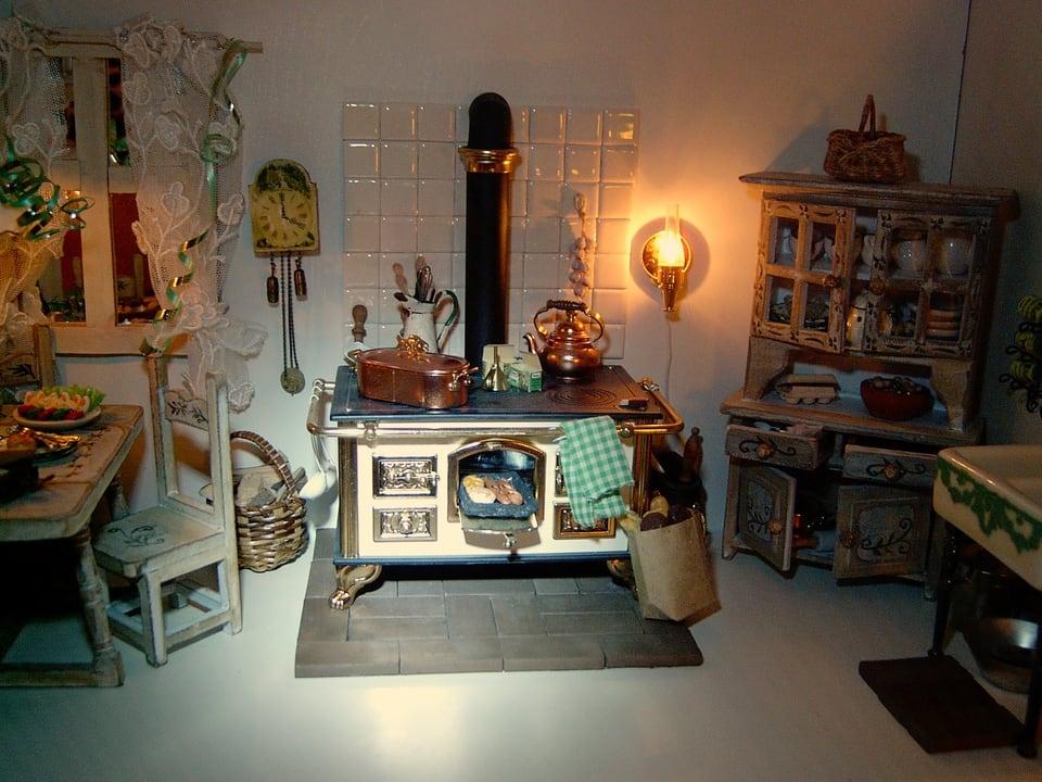 Miniature-Küche mit Herd, Küchentisch und Wanduhr.