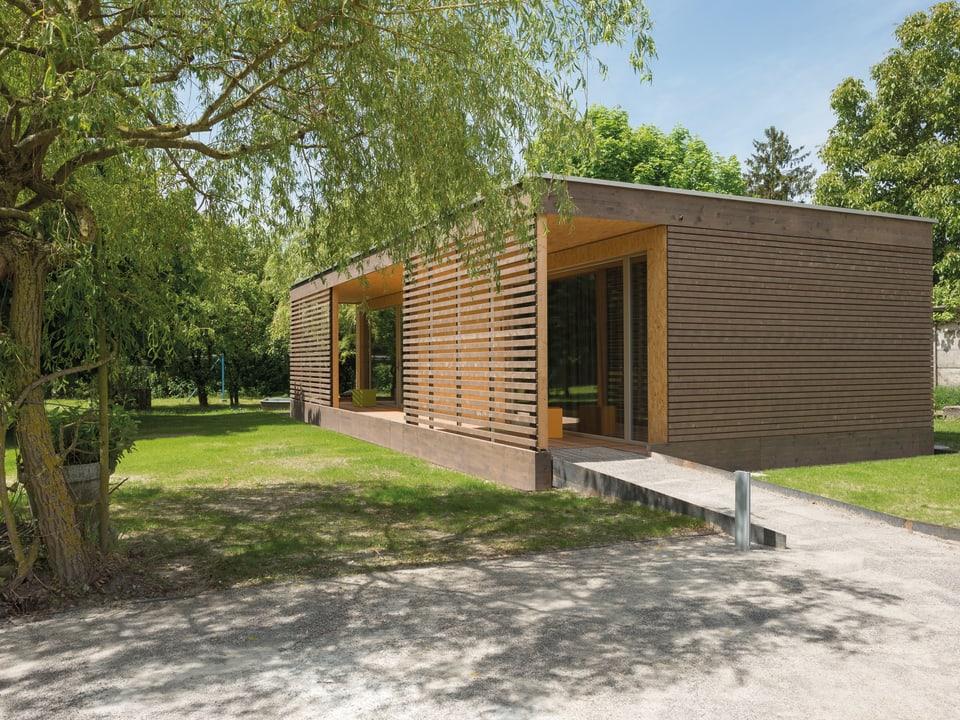 Rechteckiger Pavillon aus braunem Holz auf einer grünen Wiese.