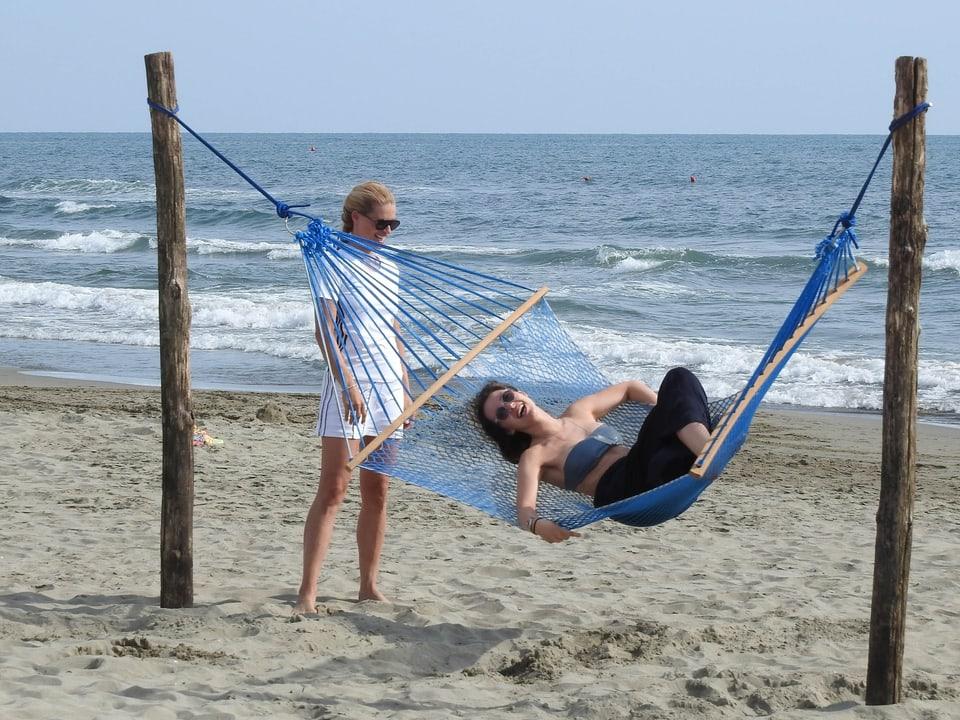 Aurora in einer Hängematte am Strand liegend. Michelle Hunziker schaukelt die Hängematte hin und her.