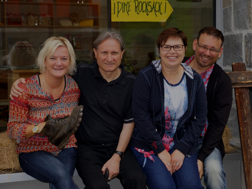 Vier Personen vor einem Holzhaus auf einer Bank.