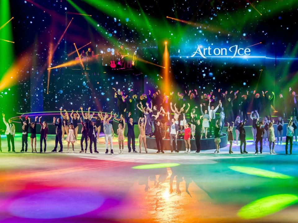 Alle Eiskunstläufer und Eiskunstläuferinnen stehen auf dem Eis und bedanken sich bei den Zuschauern.