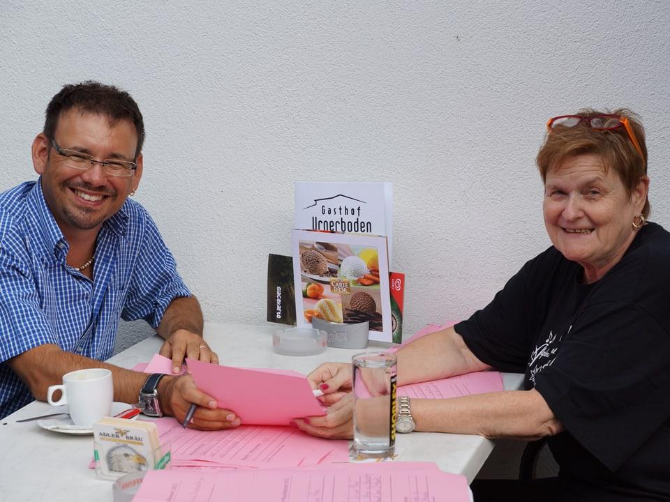 Bea Andrek und Guido Rüegge sitzen bei Tisch und lesen die Wunschliste durch.