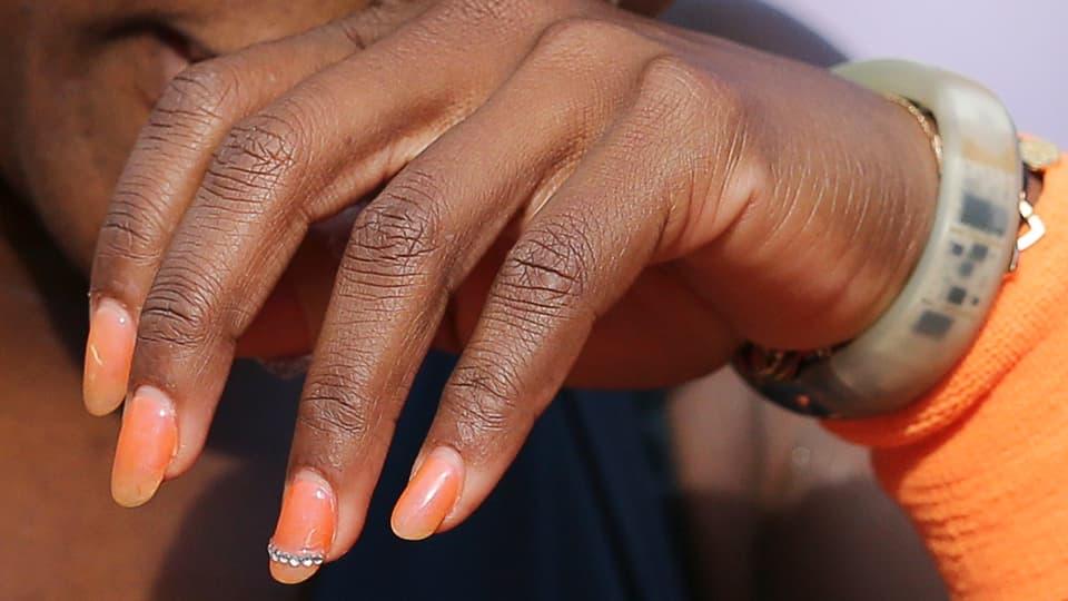 Serena Williams Hand ist in der Mitte des Bildes. Man sieht ihren orangenen Pulswärmer, der genau zu ihren orangen Fingernägeln passen.