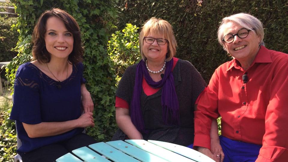Babs und Jonny sitzen im Garten mit Mona am Tisch.
