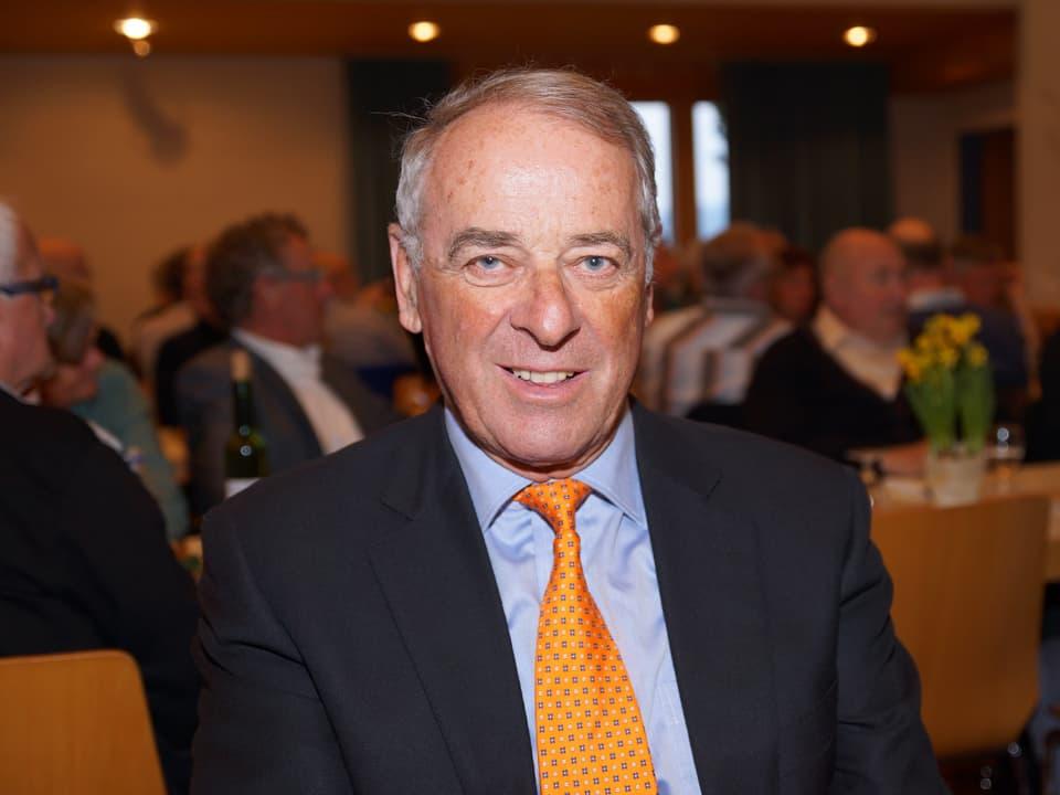 Ogi trägt orangefarbene Krawatte mit schwarzen Punkten.