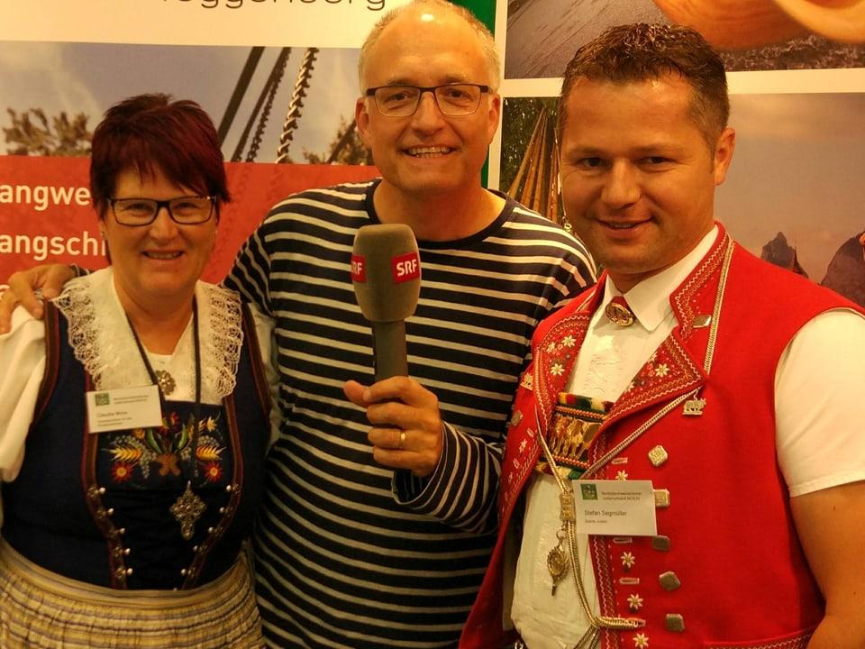 Marcel mit zwei Personen in Schweizer Trachten.
