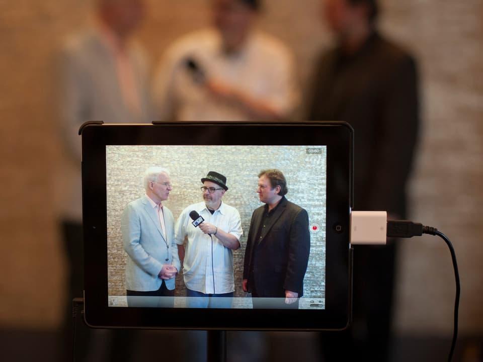 Steve Martin und Jens Krüger durch einen Monitor zu sehen mit dem Interviewer.