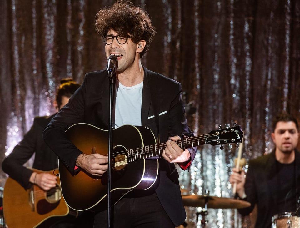 Ein Mann mit Brille und Gitarre singt auf einer Bühne.