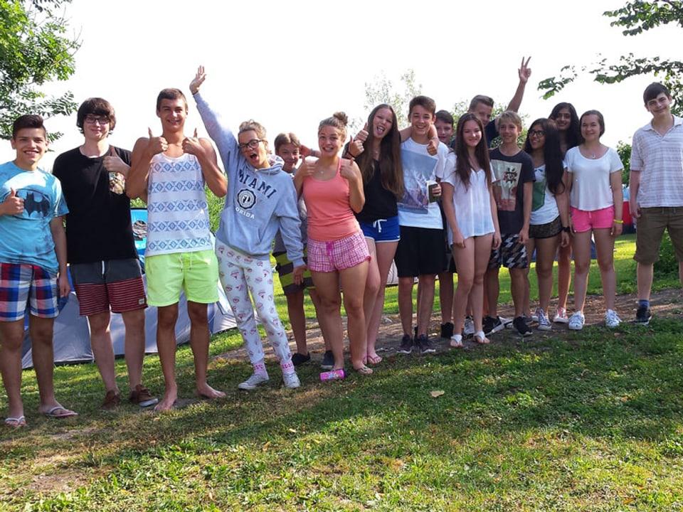 Schülerinnen und Schüler in Sommerkleidern winken in die Kamera.