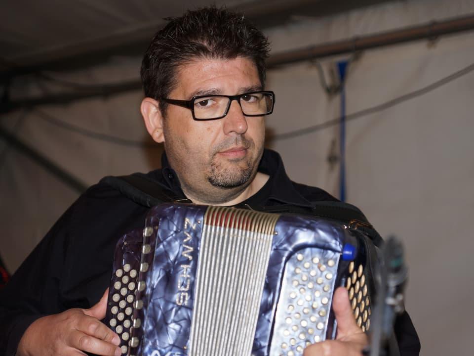Markus Flückiger mit einem blauen Akkordeon.