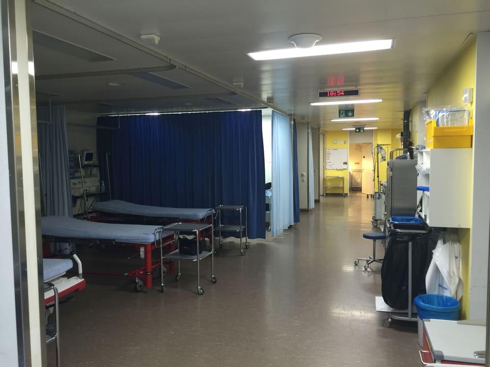 Blick in den Gang der Notfallstation. Kojen sind mit blauen Vorhängen abgetrennt.