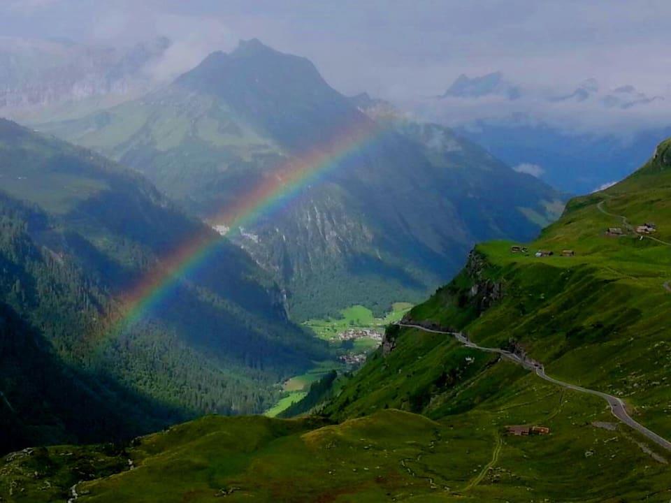 Ein Regenbogen spannt sich übers Tal.
