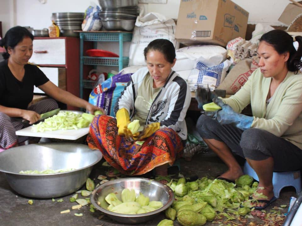 Drei Frauen sitzen am Boden und kochen.