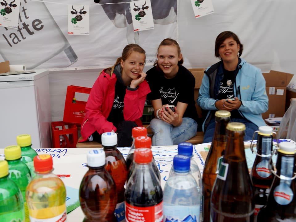 Drei Teenager sitzen hinter einem Stand, auf dem verschiedene Getränkeflaschen stehen.
