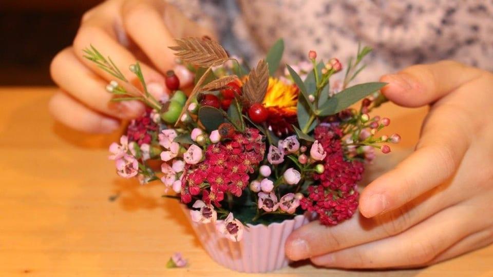 Zwei Hände stecken Blumen in eine Cupcake-Form.