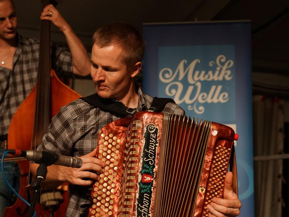 Musiker des Urschwyzer Ländlertrios mit Handorgel vor Musikwelle-Logo.