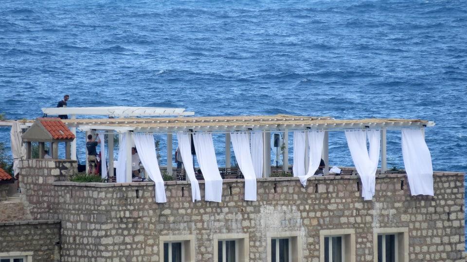 Eine Terrasse auf einem Steinhaus mit wehenden Vorhängen als Windschutz. Im Hintergrund das blaue Meer.