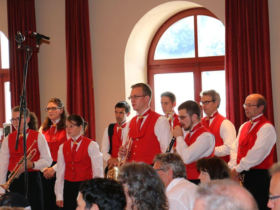 In Aula von Ilanz. Gruppe trägt rote Vestons über weissem Hemd und schwarzen Hosen.