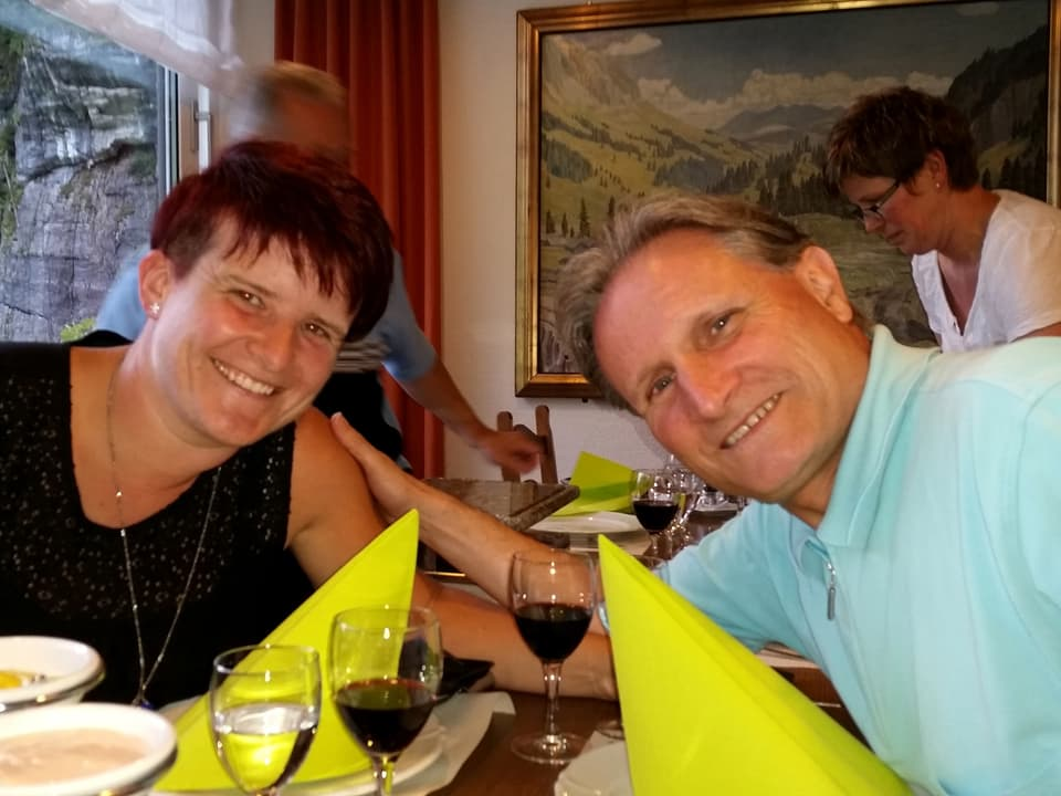 Die Beiden sitzen am gedeckten Tisch und lachen gemeinsam in die Kamera.