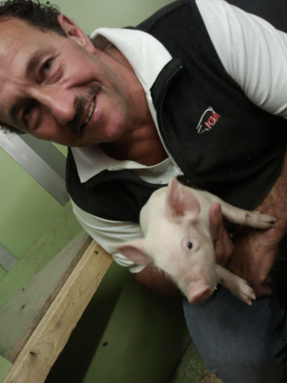Thomy Scherrer mit Tierarzt und Schulklasse vor Schweinegehege.