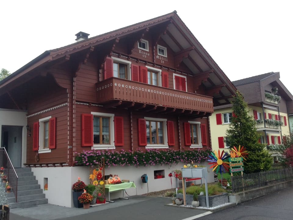 Haus im Chalet-Stil. Dunkelbraun mit roten Fensterläden.