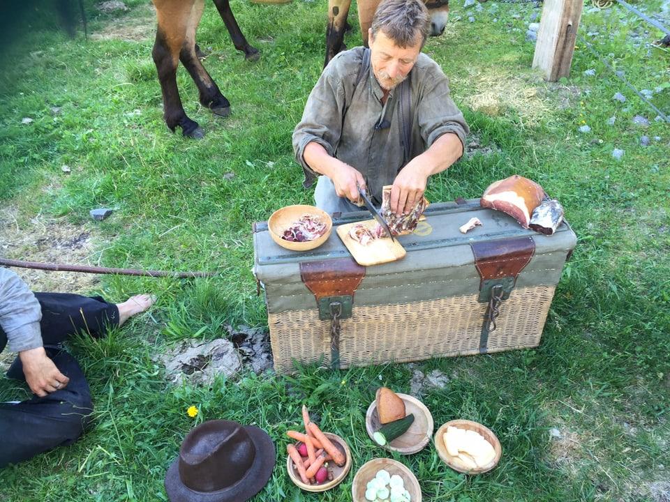 Mann schneidet auf einer Wiese Schinken auf einer Kiste. Vor ihm sehen Gefässe mit Gemüse