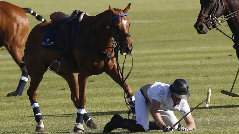Prinz Harry kniet auf dem Boden.