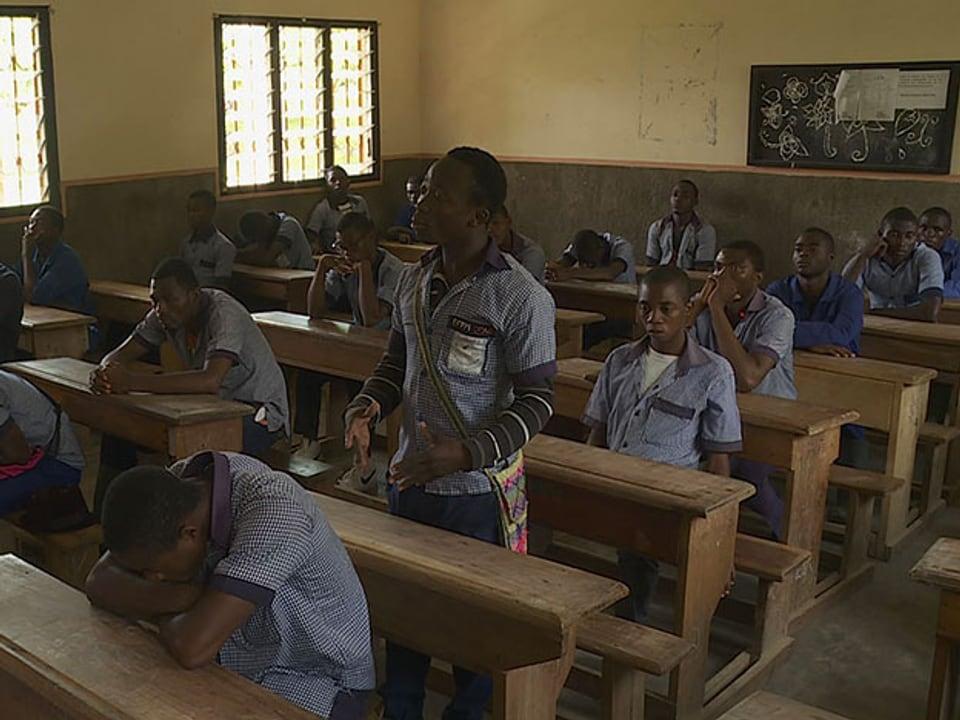 Lernender steht im Klassenzimmer.