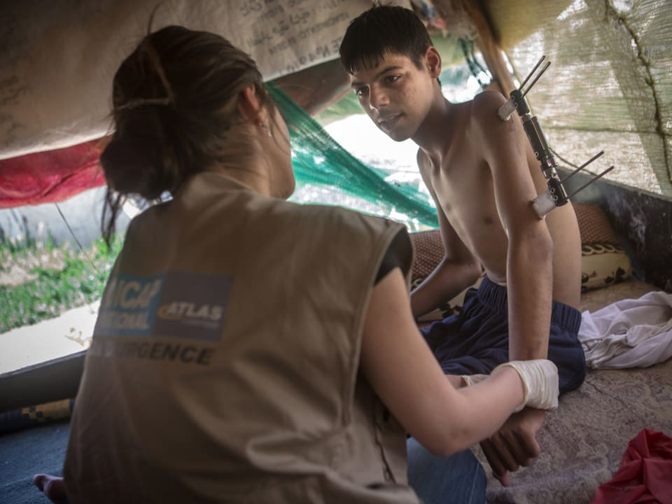 Medizinische Fachkraft mit Kriegsopfer. Der Junge hat eine Verletzung am Arm.