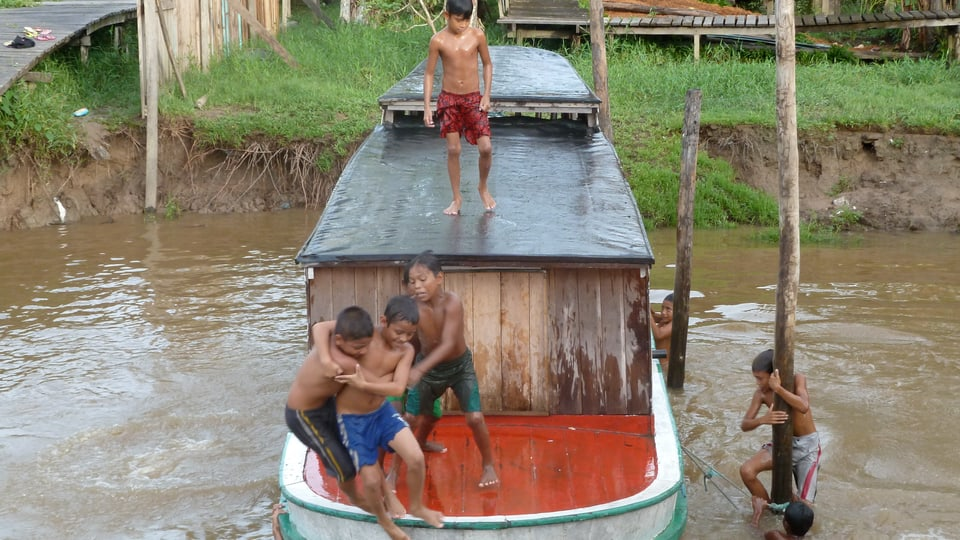 Spielende Kinder in Bailique schubsen sich gegenseitig von einem Holzschiff.