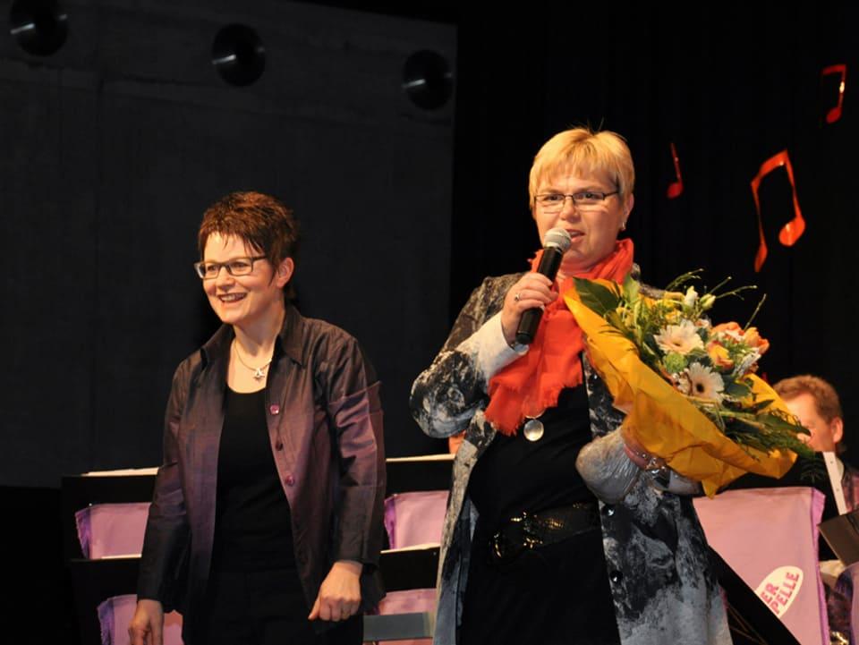 Theres Müller-Tanner und Christine Gertschen mit Blumenstrauss gemeinsam auf der Bühne.
