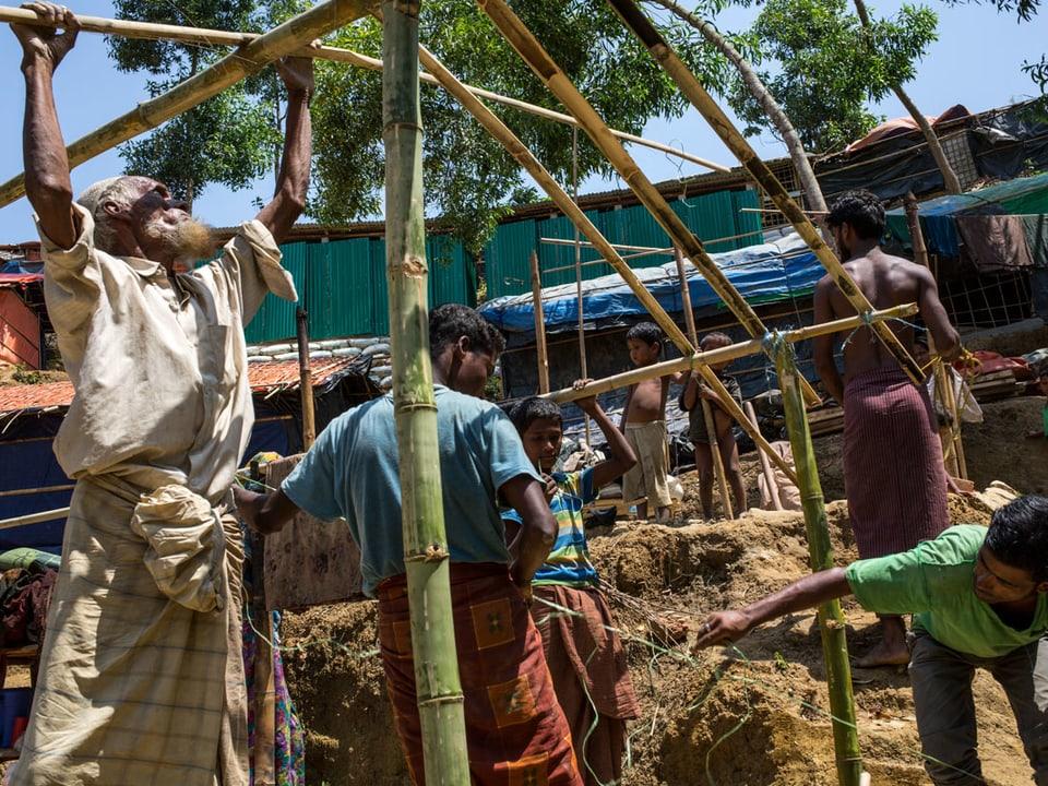 Männer bauen eine Hütte aus Bambus.
