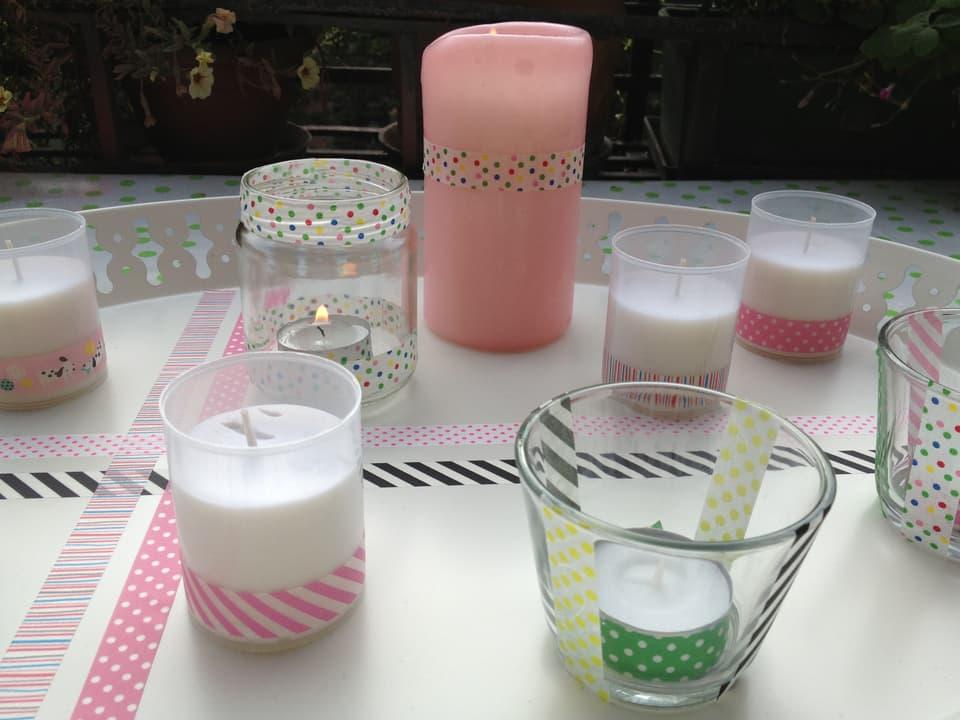 Kerzengläschen sind mit farbigen Klebstreifen verziert.