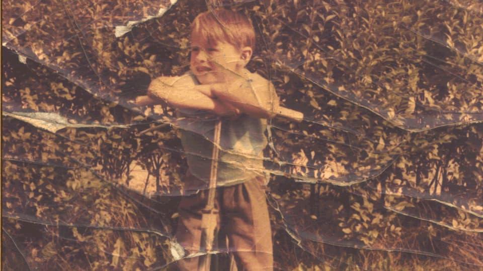 Der junge Hermann stützt sich auf einem Tretroller auf.