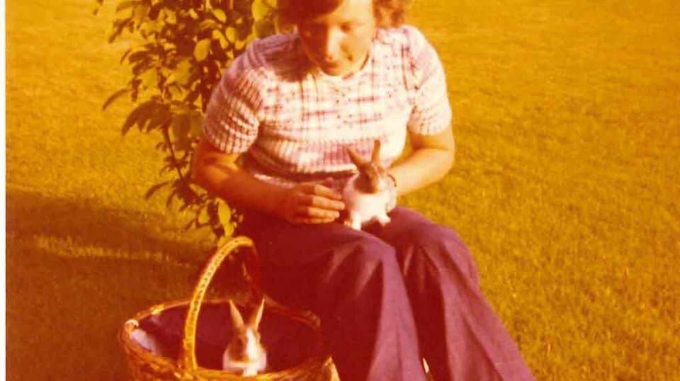 Connie streichelt ein Kaninchen auf ihrem Schoss. Ein anderes sitzt in einem Korb neben ihr.